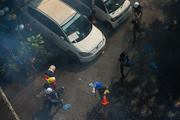2021年3月8日,仰光民眾在街頭抗議軍事政變活動中,武警頻頻發射催淚彈驅散抗議者。(STR/AFP via Getty Images)