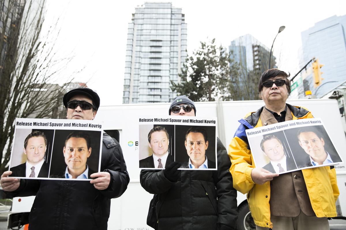 2019年3月6日,在溫哥華卑詩省最高法院外,華為首席財務官孟晚舟出庭時,抗議者拿著被中國拘留的加拿大人科夫里格和斯帕沃爾的照片。(JASON REDMOND/AFP via Getty Images)