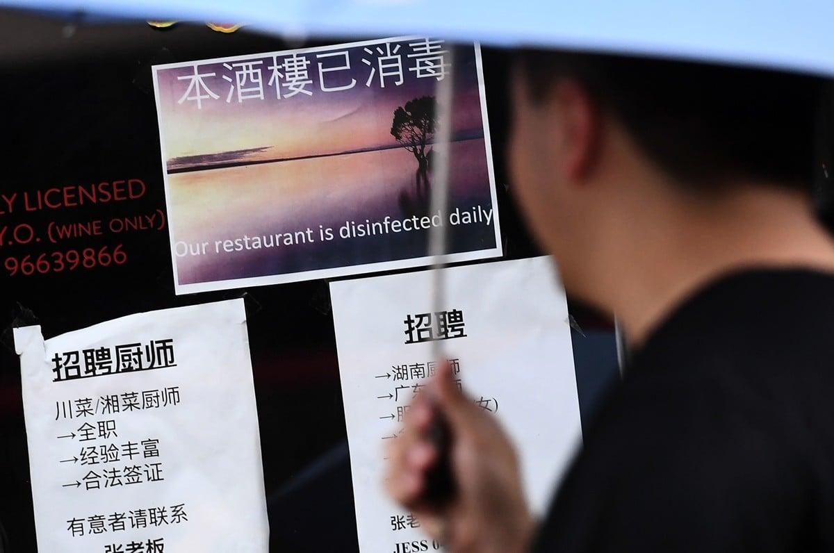 圖為2020年2月14日,一位行人在墨爾本一家標有「本樓已消毒」字樣的中國酒樓門前駐足觀看。(William WEST/AFP)