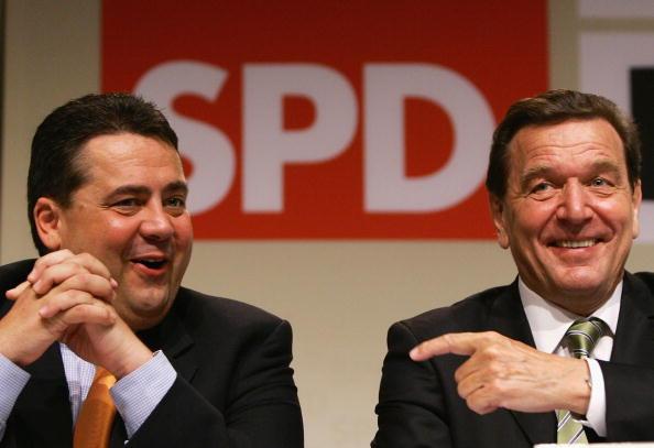 前副總理加布里爾(左)被曝光為爆發疫情的肉類加工廠工作。有人指責,他在步其黨內前輩施羅德(右)的後塵。施羅德卸任總理後立即轉入俄天然氣公司工作而備受批評。此圖攝於2005年。(Carsten Koall/Getty Images)