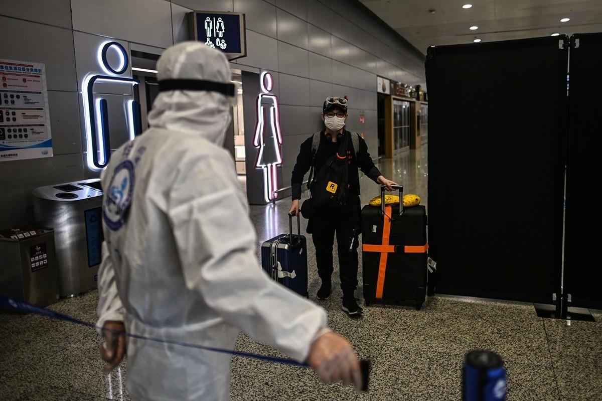圖為3月26日上海浦東國際機場的一名安檢人員控制著出口。(AFP/Getty Images)