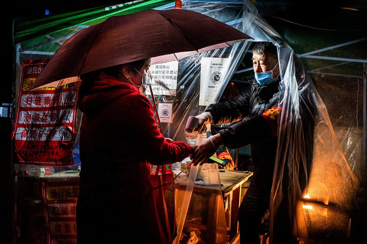 圖為4月20日牡丹江市的一個社區工作人員在檢查居民體溫。(AFP/Getty Images)