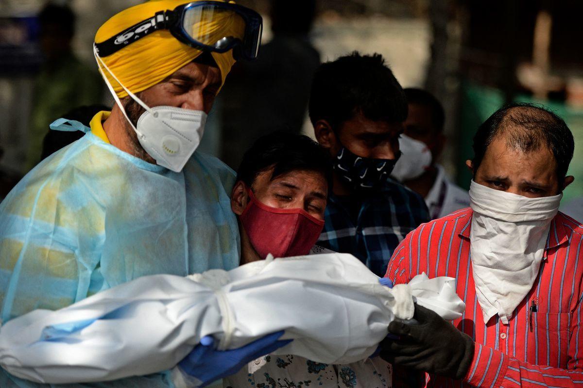 2021年5月12日,在新德里一間火葬場裏,一名男子與志願者準備為一名死於Covid-19的孩子舉行最後的哀悼儀式。 (ARUN SANKAR/AFP via Getty Images)