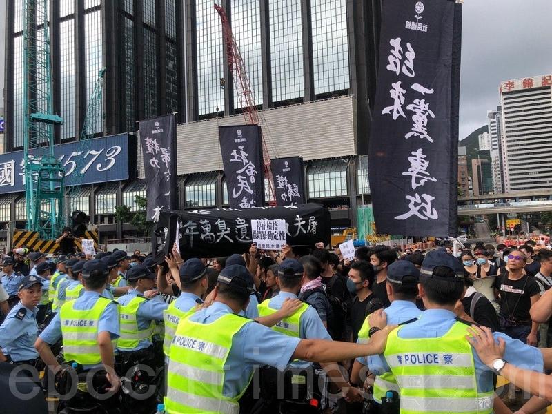 一批社民連成員抬著黑色棺材道具前往會展,遭警方築起人牆阻擋前進。前立法會議員梁國雄指,香港人已告訴世界,林鄭月娥不配做香港人的特首,共產黨也沒有兌現收回香港時的任何承諾。(佘志誠/大紀元)