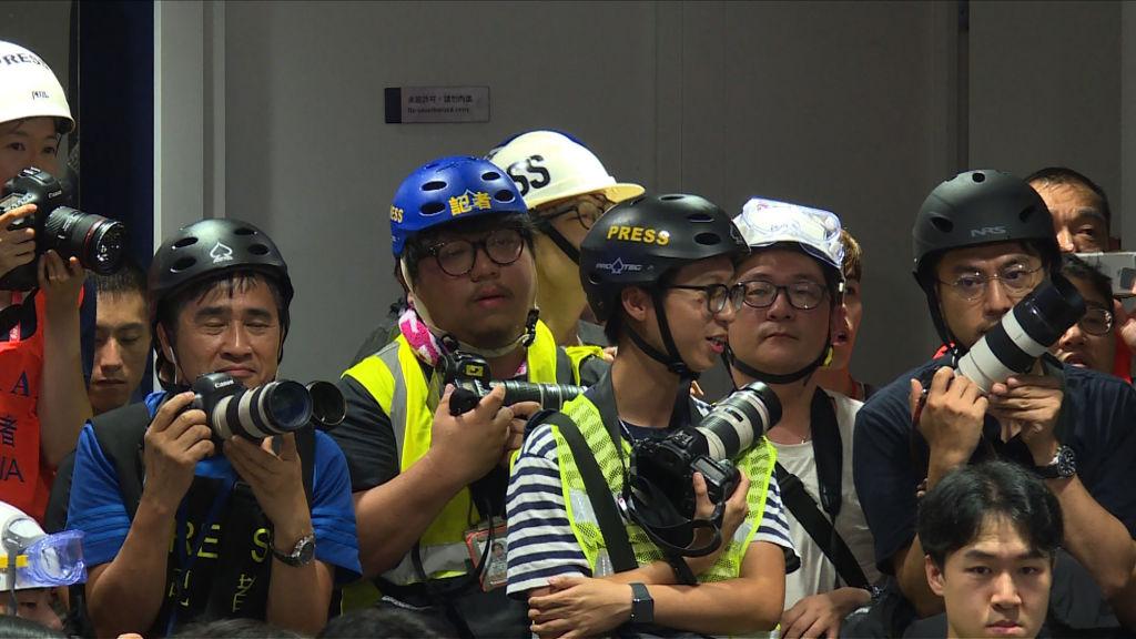 97主權移交後,香港的新聞自由逐年倒退,引發多方憂慮。圖為2019年6月13日,身穿螢光背心、佩戴頭盔的香港記者在警方的新聞發佈會上。(AFPTV TEAM/AFP/Getty Images)