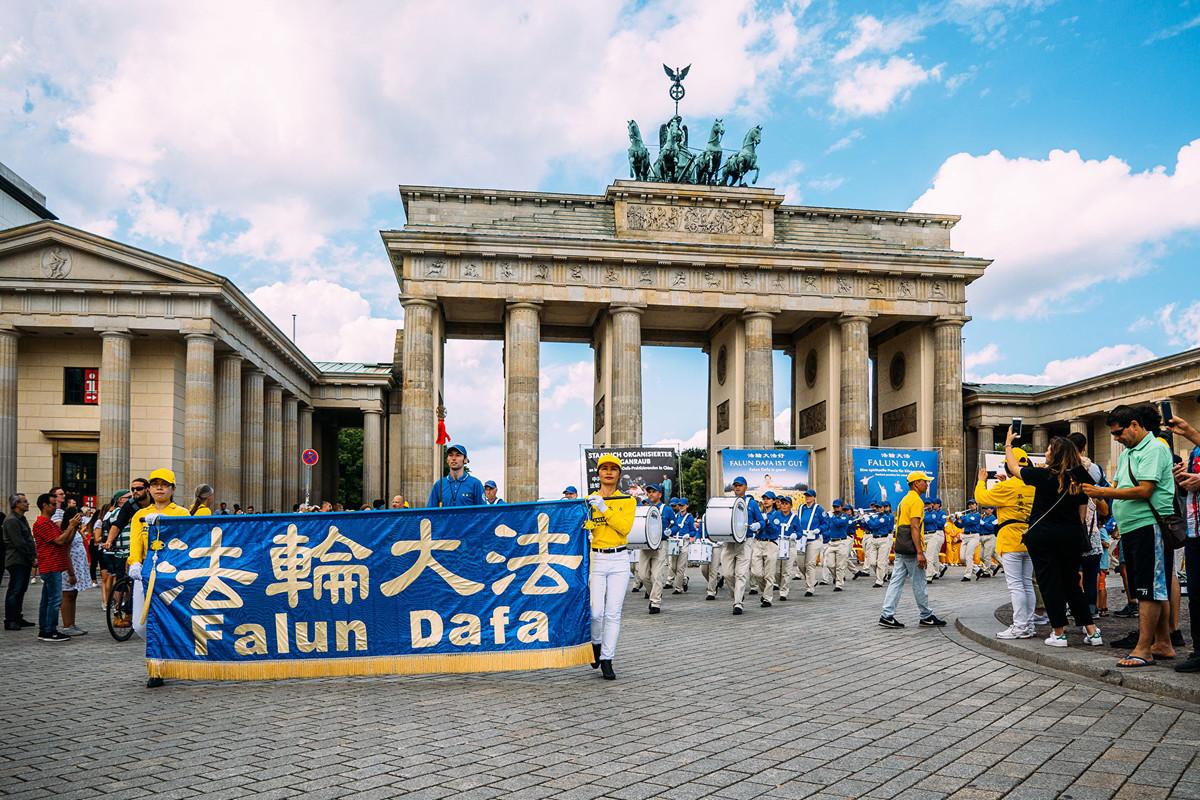 8月10日,德國部份法輪功學員在首都柏林舉行了大規模遊行集會,呼籲公眾幫助制止中共對法輪功長達20年的迫害。圖為遊行隊伍經過市中心地標建築勃蘭登堡大門。(張清颻/大紀元)