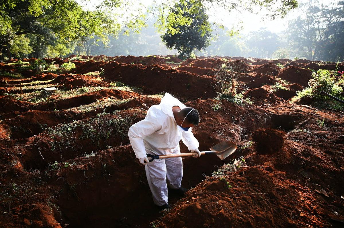 2021年5月19日,在巴西聖保羅一名身穿防護服的公墓工作人員在挖墳。當天在該公墓的57名亡者中,有23名死於COVID-19。 (Mario Tama/Getty Images)