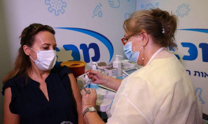 圖為2021年8月13日,以色列Rishon Lezion鎮Maccabi Health Service診所內,一名以色列衛生員在給一位女士施打第三劑輝瑞疫苗。(Ahmad Gharabli/AFP via Getty Images)