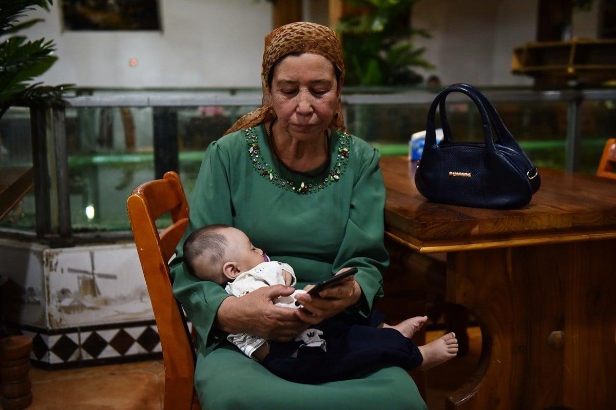 自由亞洲電台報道說,中共指派漢族「親戚」定期到新疆維族家庭進行監控,甚至與其家庭成員睡在同一張床上。圖為2019年5月31日,新疆和田市一名維族女子抱著嬰兒。(GREG BAKER/AFP via Getty Images)
