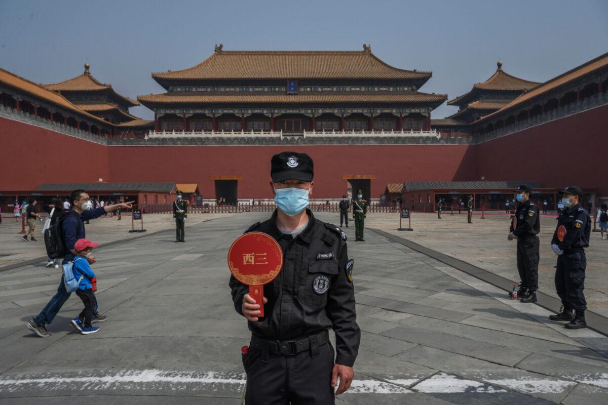 5月1日,北京故宮紫禁城開放給有限的遊客,一個戴口罩的保安站在入口處。(Kevin Frayer / Getty Images)