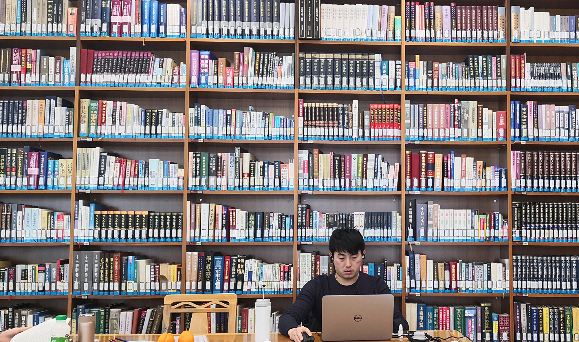 圖為2018年3月11日,首都圖書館一名男士在書架前使用電腦。(大紀元資料室)
