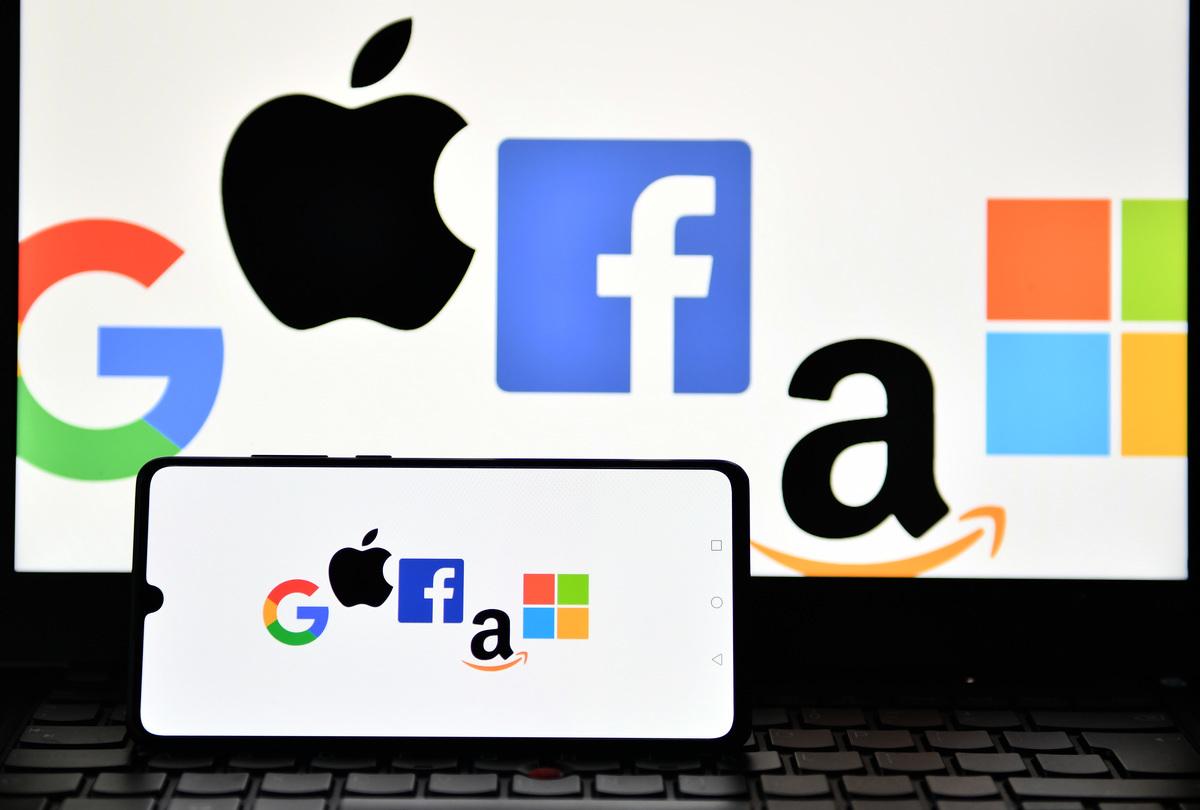 2020年12月18日攝於倫敦,照片顯示了Google、蘋果、Facebook、亞馬遜和微軟的logo顯示在手機和手提電腦屏幕上。(Justin Tallis/AFP via Getty Images)