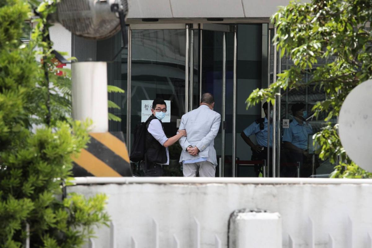 香港《蘋果日報》創辦人黎智英被扣上手銬,押送到《蘋果日報》大樓內協助查證。(中央社)