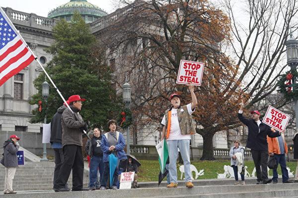 2020年11月30日,賓州議會大廈外的抗議者高舉「制止竊選」的標語牌。(李臻婷/大紀元)