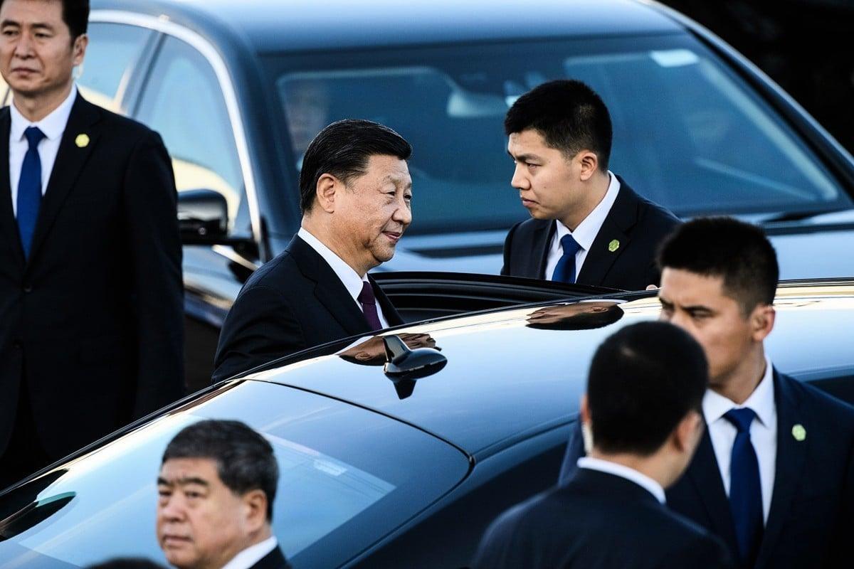 12月18日,習近平到達澳門。圖為習準備坐車離開機場,保安人員圍在周圍。(ANTHONY WALLACE/AFP via Getty Images)