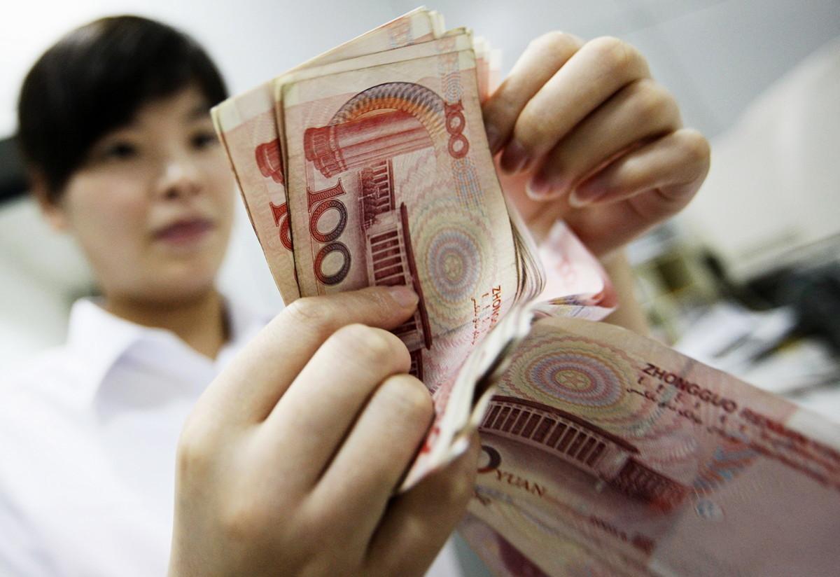 中共《環球時報》總編輯胡錫聲稱,如果中美經濟脫鉤,中共能因應短期困難。美國對沖基金大佬巴斯回應說,這是中共宣傳的一大笑話。圖為2010年8月4日,中國安徽省一家銀行的行員在清點人民幣鈔票。(STR/AFP/Getty Images)