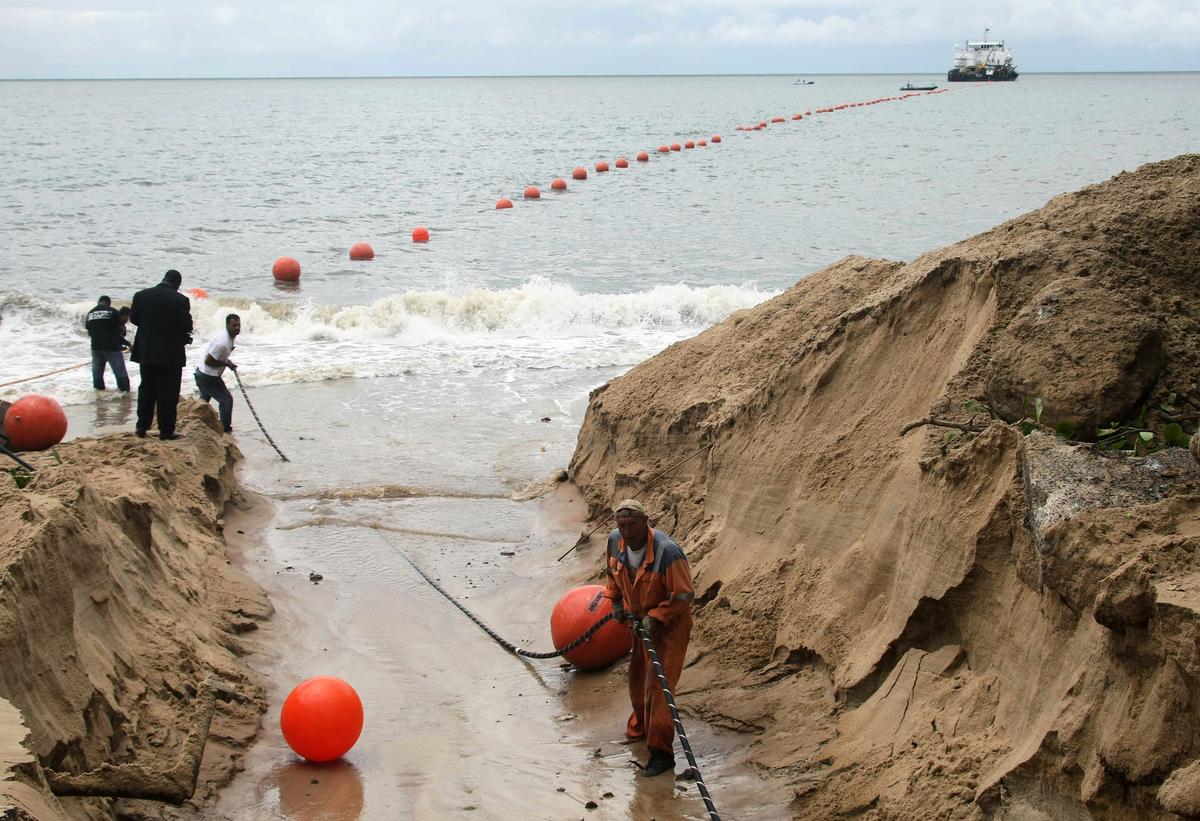 圖為技術人員2011年10月27日在利伯維爾(Libreville)海濱展示海底電纜。(AFP)
