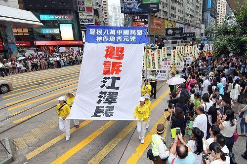 法輪功學員舉辦遊行活動,打出「全球公審江澤民」內容的橫幅。(大紀元)