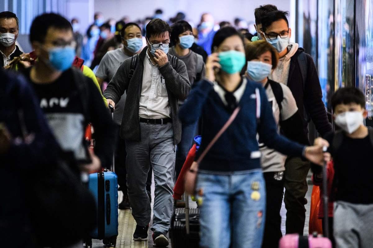 圖為武漢肺炎大規模爆發後,2020年2月3日在香港羅湖過境點關閉前幾個小時,乘客從深圳到達香港的羅湖地鐵站時戴上了防護口罩。(ANTHONY WALLACE/AFP via Getty Images)