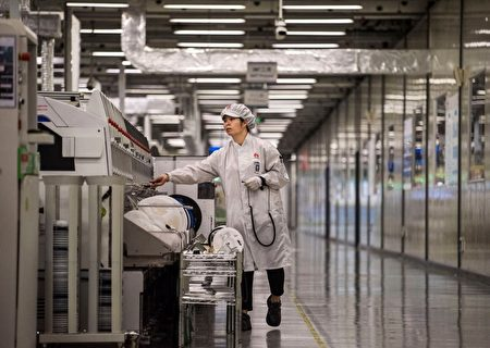 示意圖,圖為深圳東莞華為生產園區,一名工人在生產線末端給智能手機打包。(Kevin Frayer/Getty Images)