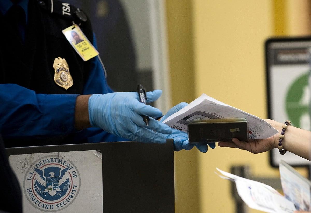 自2020年10月1日開始,旅客如果沒有符合《真實身份法》(Real ID Act)的駕照或其它身份證件(REAL ID),無法搭乘美國國內航班。圖為美國TSA(運輸安全管理局)官員在檢查旅客證件。(JIM WATSON/AFP via Getty Images)