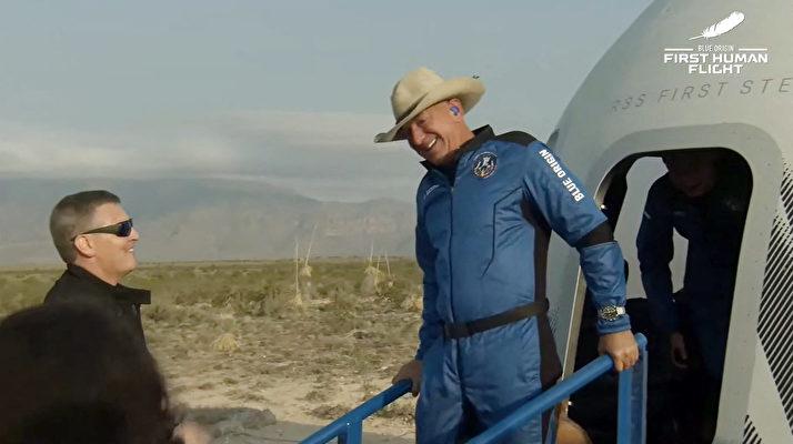 這張來自藍色起源公司的圖片顯示,2021年7月20日,該公司可重複使用的新謝潑德(New Shepard)飛船從太空返回,並在德薩斯州的範霍恩(Van Horn)安全著陸。謝菲貝索斯(Jeff Bezos,右)等人走出太空艙。——藍色起源公司首次載人任務是從德薩斯州西部起飛,達到65英里(106公里)的高度後返回地面,來回飛行時間持續11分鐘。這一天是阿波羅11號人首次登月52周年。(Handout / BLUE ORIGIN / AFP)