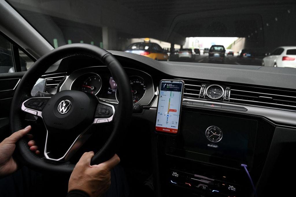 2021年7月5日,一名司機在北京街頭開車行駛時,正使用其智能手機上的滴滴出行打車應用程式的地圖。(GREG BAKER/AFP via Getty Images)