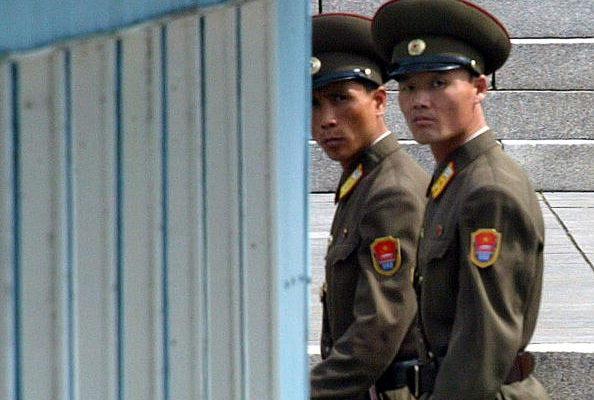 最新消息稱,在俄羅斯務工的10名北韓工人集體叛逃,正在等待前往南韓定居。圖為北韓士兵巡邏板門店的邊境村庄時,兩名北韓士兵在向南韓看。(Getty Images)
