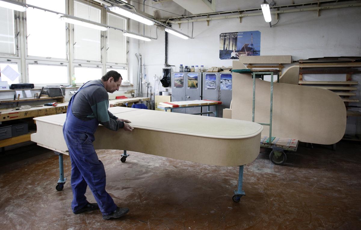 圖為2009年2月捷克知名鋼琴製造商佩卓夫(Petrof)的工廠內,員工正在組裝鋼琴。佩卓夫以手工生產鋼琴聞名,其鋼琴售價遠高於平均水平,近年來每年生產大約7,000架鋼琴,大部份用於出口。(Milan Jaros/AFP)