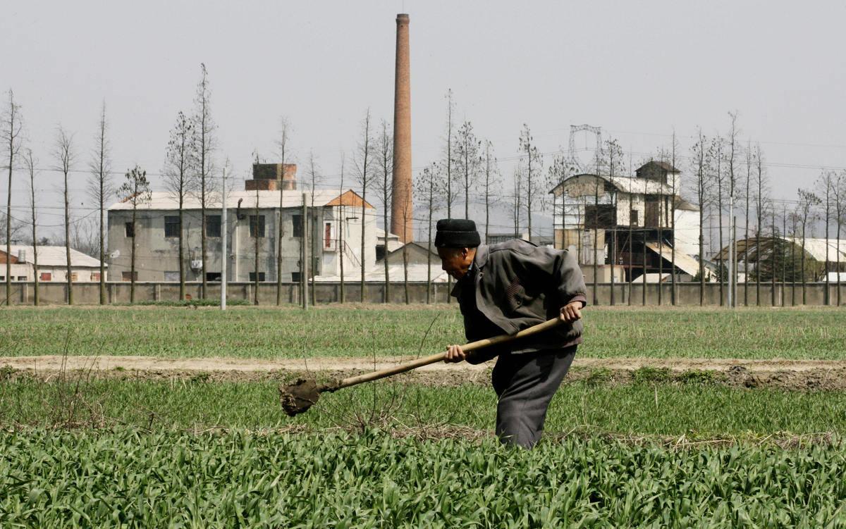 江蘇宜興農民的農田緊臨著化工廠(AFP/Getty Images)