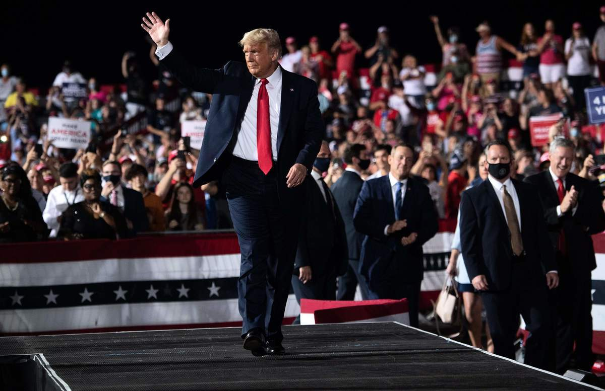 圖為2020年10月21日,美國北卡羅來納州加斯托尼亞(Gastonia),總統特朗普在加斯托尼亞市政機場舉行競選集會後,他向支持者揮手致意。(SAUL LOEB/AFP via Getty Images)
