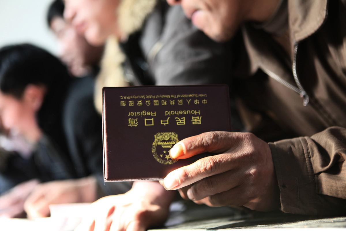 大陸開放申辦「港澳台居民居住證」,而大陸的戶籍管理歷來受輿論詬病。圖為大陸一農民工手持戶口簿。(大紀元資料室)