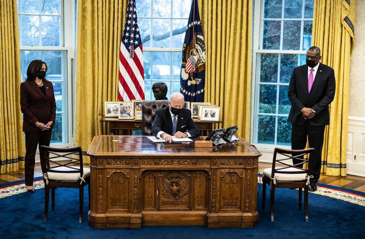 2021年1月25日,在副總統賀錦麗(左)和國防部長奧斯汀(Lloyd Austin,右)的見證下,拜登總統(中)簽署行政令,推翻特朗普禁止變性人參軍的政策。(Photo by Doug Mills-Pool/Getty Images)