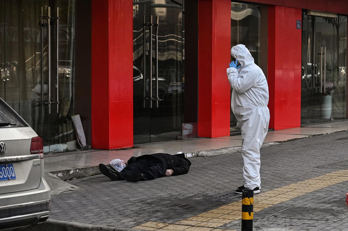 2020年1月30日,法新社記者在武漢直擊、拍攝到一名戴著口罩老人倒斃在武漢一家醫院附近的一條街上。(Hector RETAMAL/AFP)