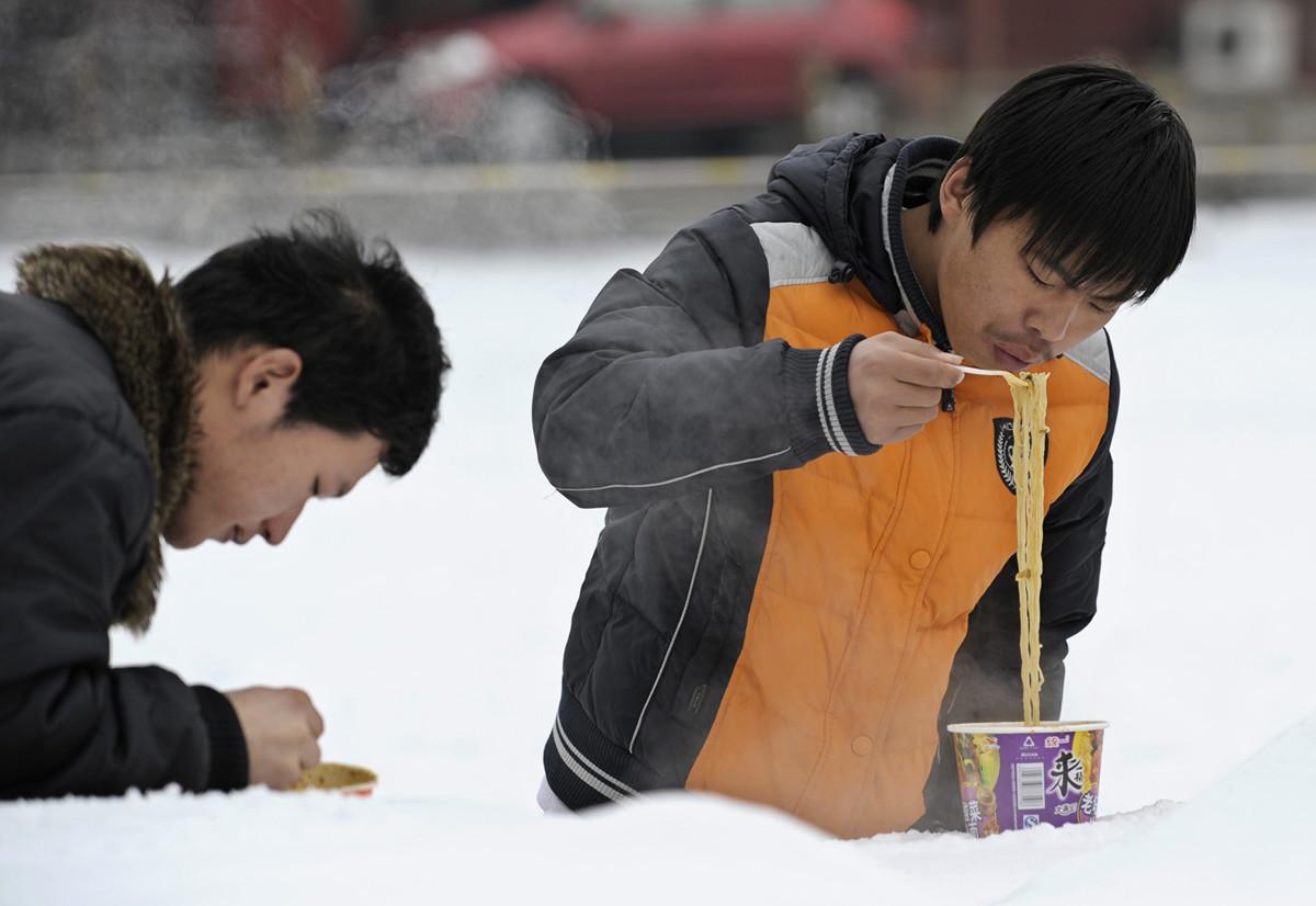 瑞士信貸專家認為,中國泡麵銷量增加,顯示中國出現消費降級現象。圖為,2名遊客在一個漫天飛舞的日子於北京天安門廣場上吃公仔麵。 (LIU JIN/AFP/Getty Images)