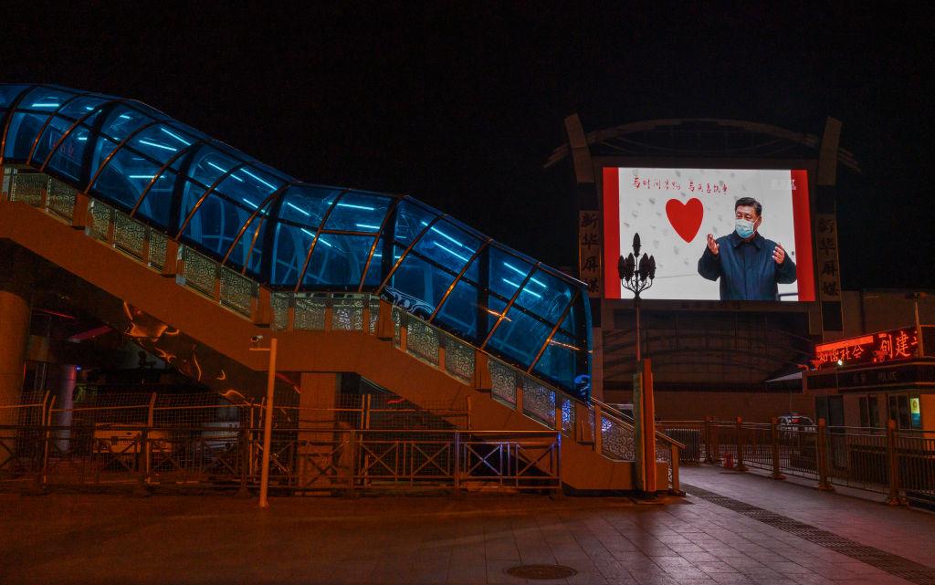 圖為3月13日,北京一座空空的車站旁,標牌上顯示習近平戴著口罩的圖像。(Kevin Frayer/Getty Images)