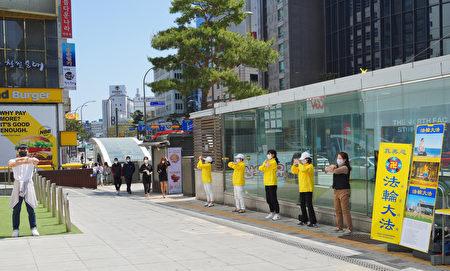 在南韓政府的防疫政策下,法輪功學員分散舉行紀念活動,圖為學員在首爾發佈會周邊集體煉功。(李裕貞/大紀元)