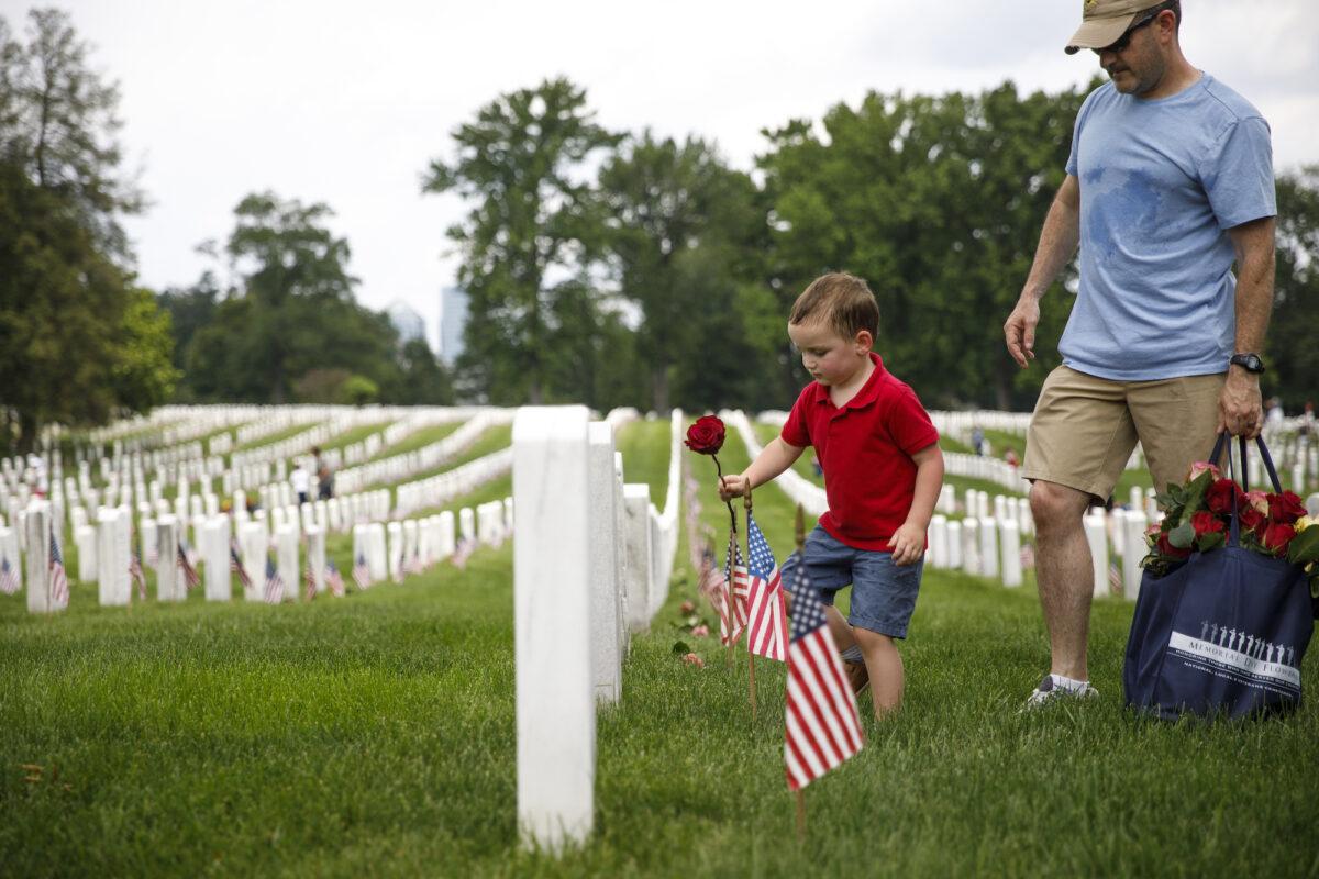 2019年5月26日,陣亡將士紀念日前夕,在阿靈頓國家公墓的一個志願者活動中,來自弗州斯普林菲爾德鎮(Springfield)的四歲的馬修‧墨菲(Matthew Murphy)與父親凱文‧墨菲(Kevin Murphy)一起,將一支玫瑰花放在一座墓碑前。(Tom Brenner/Getty Images)