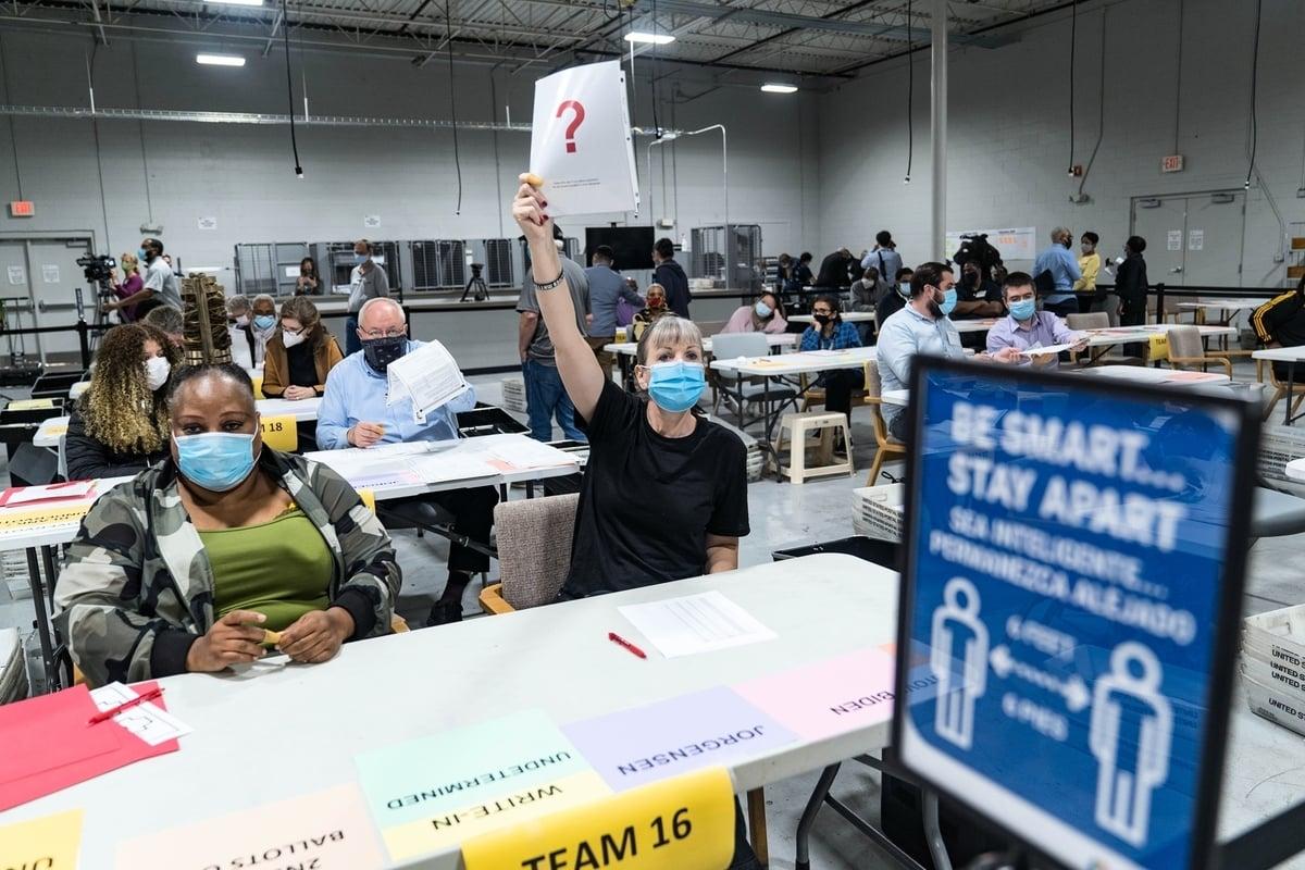 圖為2020年11月13日,在佐治亞州勞倫斯維爾開始重新點票時,格溫內特縣的一名工人舉了一張紙,表明她發現了一個問題。(Megan Varner/Getty Images)