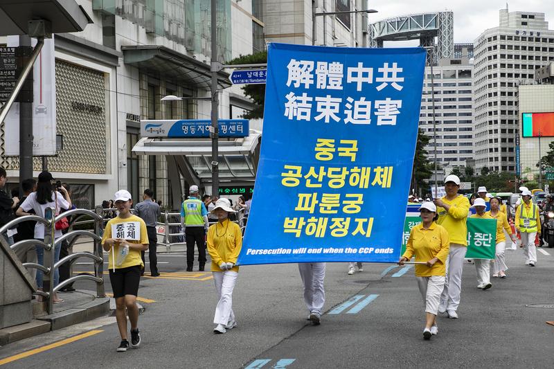 2019年7月20日,南韓法輪功學員聚集在首爾市中心舉行法輪功反迫害20年大遊行。圖為「解體中共 結束迫害」的大型豎幅。(全景林/大紀元)