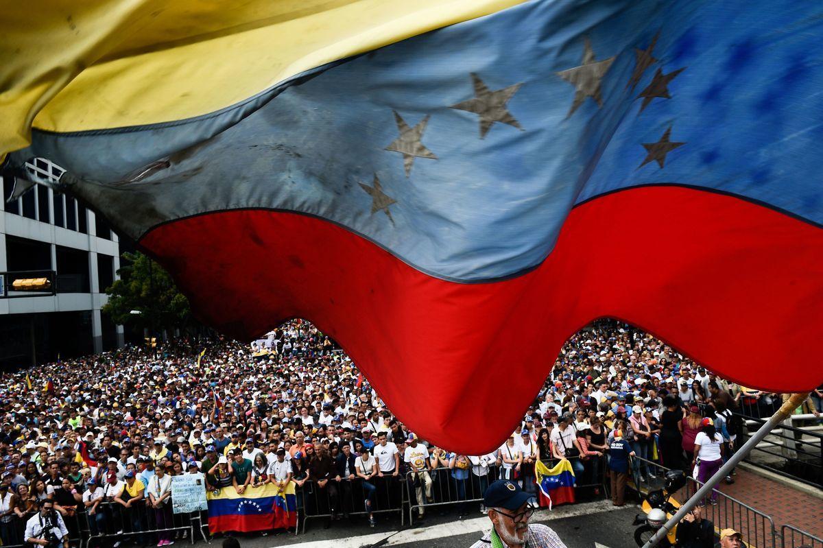 35歲的委內瑞拉反對派,國民議會議長瓜伊多(Juan Guaido,中)1月23日在數万名支持者面前宣布,根據委內瑞拉憲法接管國家行政權力,並成立過渡政府,舉行大選。 當天數万人在委內瑞拉首都加拉加斯的集會現場。(FEDERICO PARRA/AFP/Getty Images)