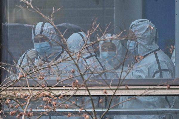 2月2日,世衛專家小組的成員穿著防護服參觀湖北省動物疾病預防控制中心,調查中共病毒的來源。(HECTOR RETAMAL/AFP via Getty Images)