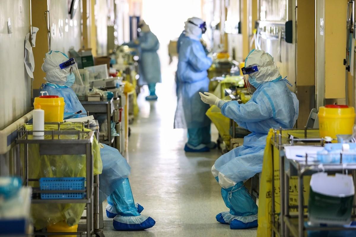 圖為3月6日武漢醫務人員在病房外面等候。(AFP/Getty Images)