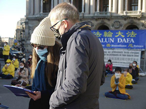 在巴黎歌劇院廣場,人們在徵簽表上簽字,支持法輪功反迫害。(明慧網)