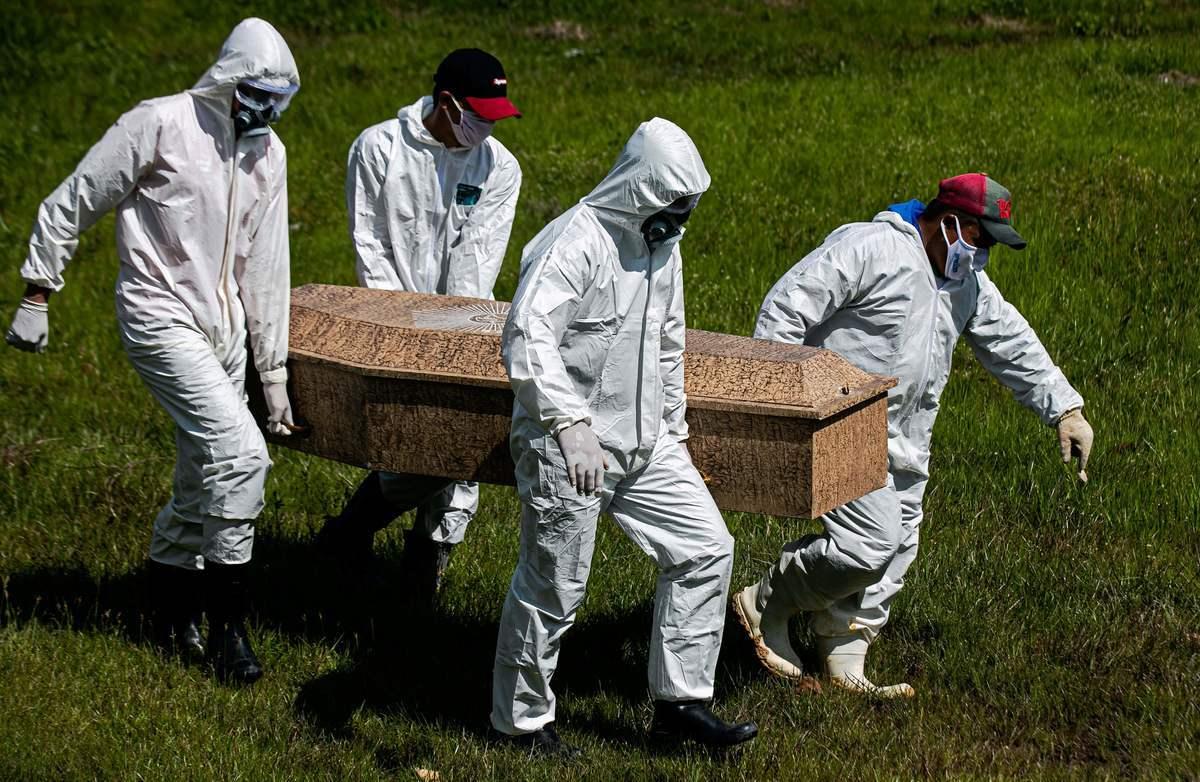 2020年6月8日,在巴西帕拉州佈雷夫斯的雷坎托·達和平市政公墓,公墓工作人員穿著防護服正在為死於COVID-19的人舉行葬禮。(TARSO SARRAF / AFP)