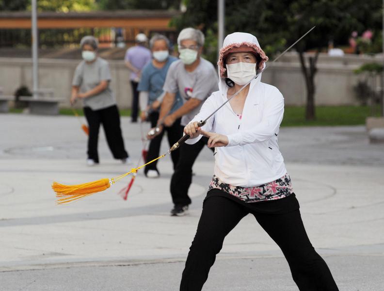 台灣中共病毒(俗稱武漢病毒、新冠病毒、COVID-19)疫情嚴峻,全國三級警戒延至2021年7月12日,桃園6月29日上午陽光露臉,不少年長者戴著口罩至戶外空間活動筋骨。(中央社)