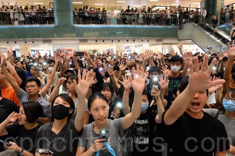 2019年9月11日,香港市民在沙田新城市廣場齊唱《願榮光歸香港》,市民抬起手臂,展開手掌,代表「五大訴求、缺一不可」。(黃曉翔/大紀元)