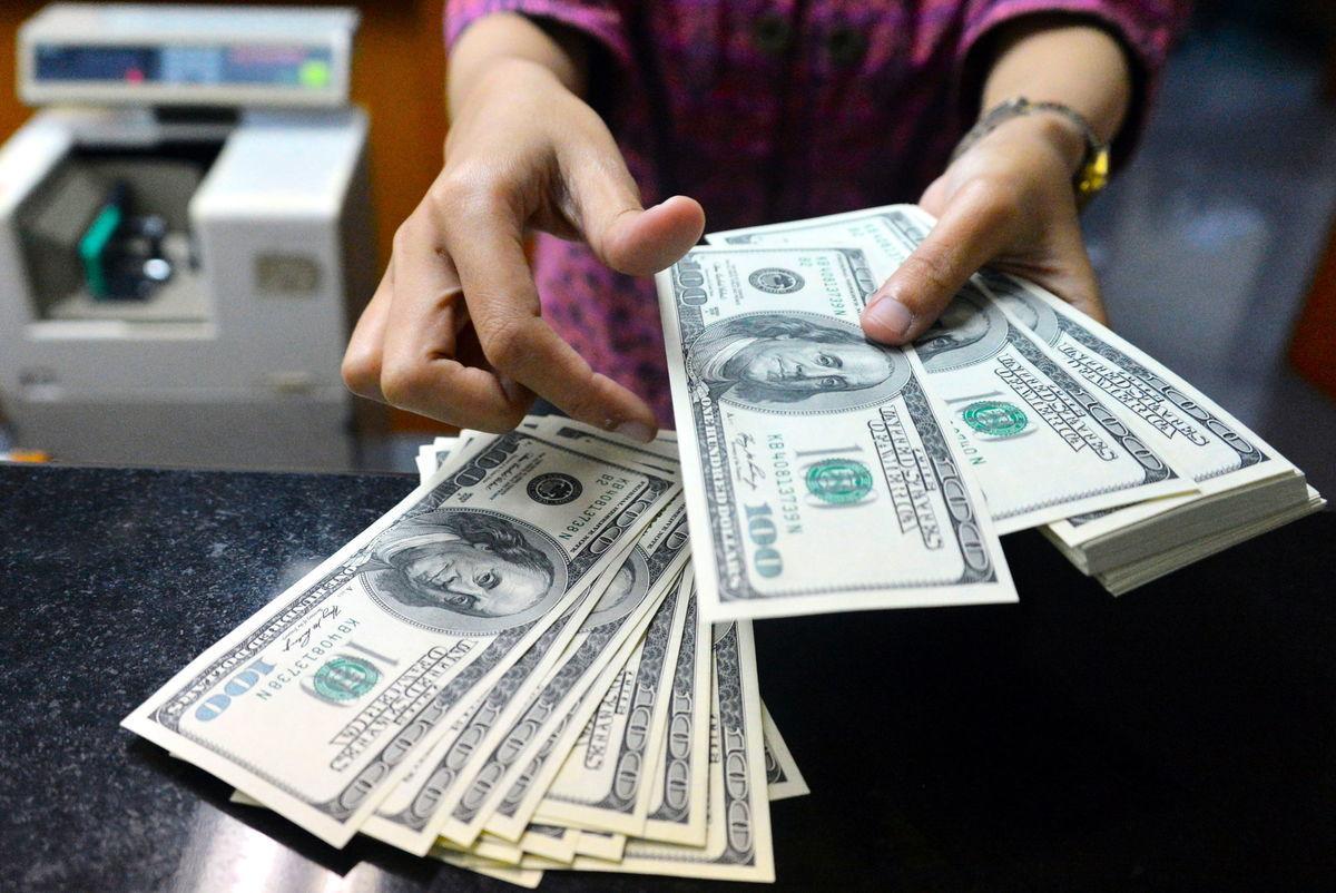 商務部10月29日公佈第三季經濟初步數據,其國內生產總值(GDP)季度增長7.4%,折合年率增長33.1%,創下有紀錄以來最大反彈。圖為銀行員工清點美元紙幣。(BAY ISMOYO/AFP/Getty Images)