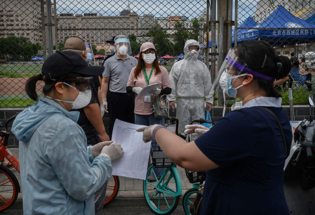 2020年6月15日,北京防疫人員對接觸過新發地批發市場的市民進行核酸檢測。(Kevin Frayer/Getty Images)