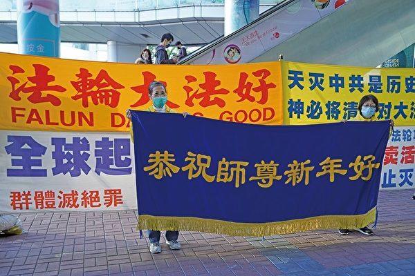 在紅磡真相點講真相的法輪功學員恭祝李洪志師父新年快樂。(大紀元)